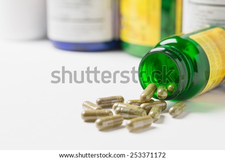 Dietary supplement capsules spilled from a bottle onto a table. Shallow depth of field. - stock photo