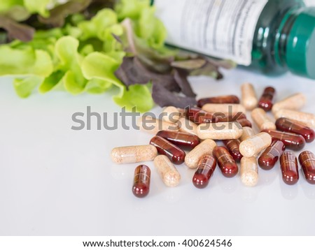 Dietary supplements Capsules and its bottles with Fresh vegetables. Concept image of good health with dietary supplements. - stock photo