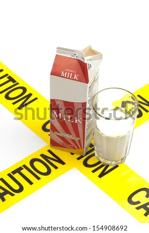 Dietary warning, lactose intolerance allergy warning (generic carton of milk with glass filled with milk on top of yellow caution tape) - stock photo