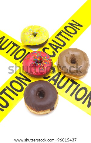 Dietary warning, or high calorie/high, fat junk food warning (Donuts with yellow caution tape) - stock photo