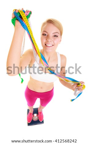 Dieting and slimming. Happy joyful young woman girl holding tape measure on weighing scale. Healthy lifestyle concept. Isolated on white background.  - stock photo