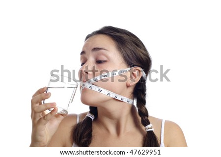 Dieting concept, cute girl had her mouth closed by measuring tape. - stock photo
