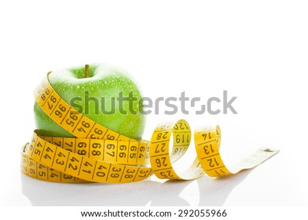 Dieting concept. Green apple with measuring tape on white background