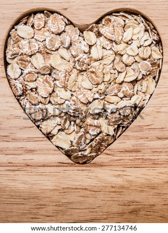 Dieting healthcare concept. Oat cereal oatmeal heart shaped on wooden surface. Healthy food for lowering cholesterol. - stock photo