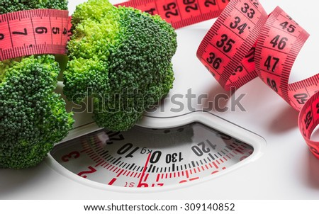 Dieting healthy eating slim down weight control concept. Closeup green broccoli with measuring tape on white scales - stock photo