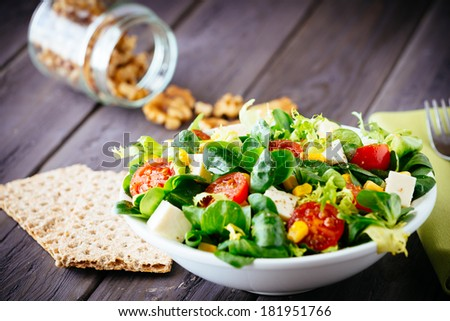 Dieting healthy salad and crackers on rustic wooden table. Mixed greens, tomatos, diet cheese, olive oil and spices for healthy lifestyle concept. - stock photo