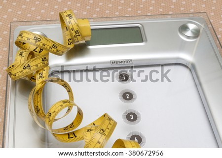 Dieting weight-loss slim down concept. Closeup measuring tape on white weight scale - stock photo