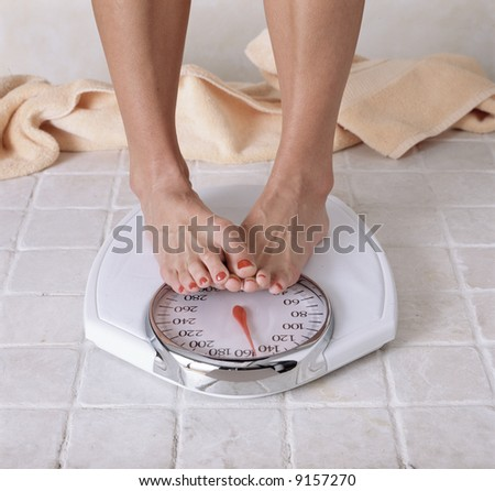 Dieting woman's feet on a white scale in a bathroom.