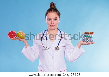 Dietitian nutritionist woman holding diet weight loss tablets pills and grapefruits. Choice between natural and synthetic way of slimming dieting. Health care. - stock photo