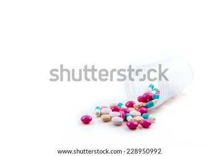 diferent Tablets pills capsule spilled from pill bottle  - stock photo