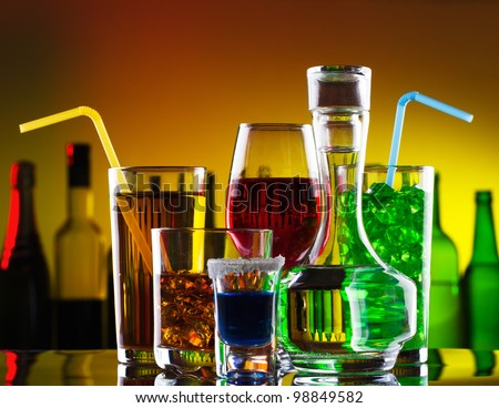 Different alcohol drinks and cocktails on bar - stock photo