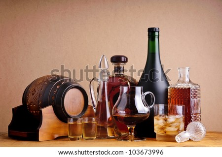 different alcoholic drinks, brandy, cognac and whiskey on a wooden background - stock photo