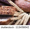different assortment fresh bread and wheat ears - stock photo
