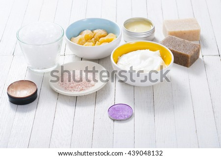 different bath salts, bees wax , makeup base, powder compact, soaps and cosmetic creams on white wooden background