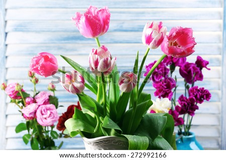 Different beautiful flowers in vases on wooden background - stock photo