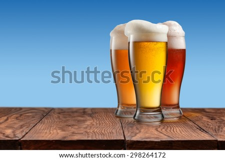 Different beer in glasses on empty wooden table and simple blue background - stock photo
