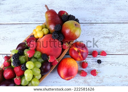 Different berries and fruits on wooden table close-up - stock photo