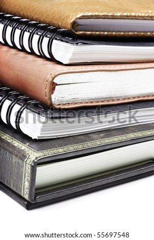 Different books stacked up on top of each other on a white background with space for text