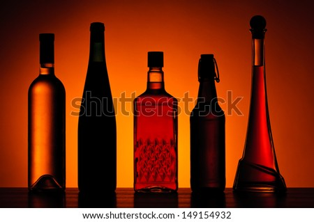 different bottles of alcoholic drinks on a wooden table - stock photo