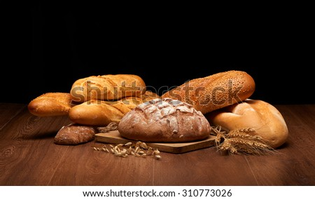 Different bread and wheat on dark wooden table background - stock photo
