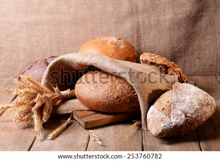 Different bread on table on sack background - stock photo