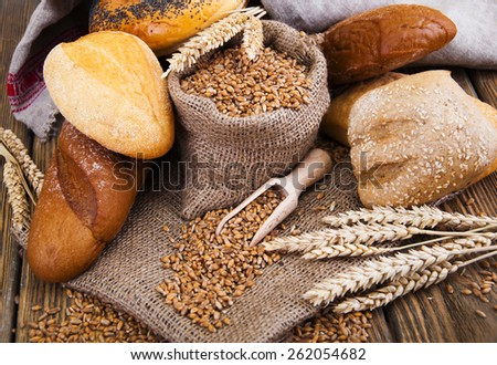 Different bread with wheat in a small bag , on a wooden background - stock photo