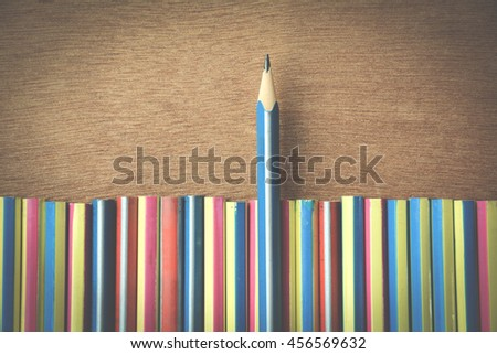 different businessman concept.blue pencil standing out from a bunch pencils on wooden floor. Vintage Style - stock photo