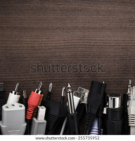 different cables on the brown wooden table - stock photo