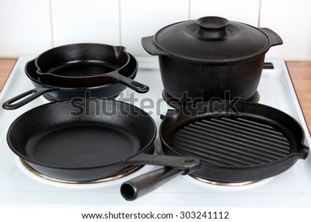Different cast iron cookware on electric stove  - stock photo