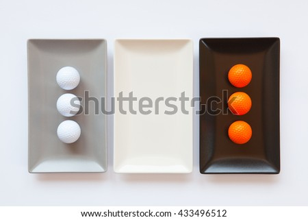 Different ceramic dishes with golf balls on over white background, rectangle dish