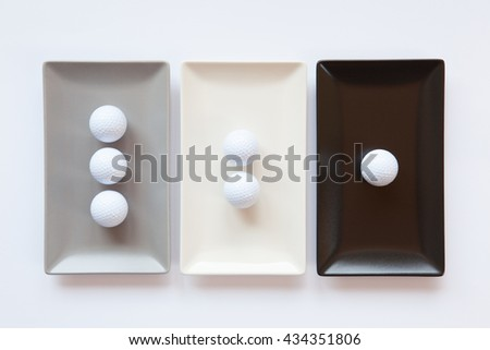 Different ceramic dishes with golf balls on over white background, rectangle dish - stock photo