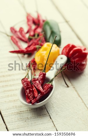 Different chili peppers on wooden background. Retro style. Selective focus. - stock photo