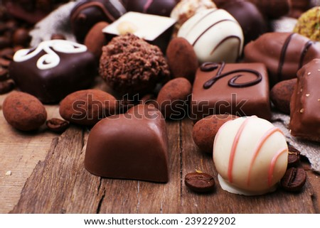 Different chocolates with coffee beans on grey fabric on wooden background - stock photo