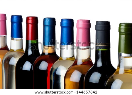 Different closed wine bottles in a row against white background - stock photo