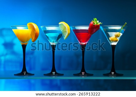 Different cocktails garnished with fruits on blue background - stock photo