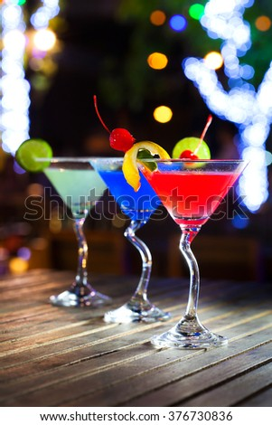 Different cocktails with fruits on wood table at restaurant - stock photo