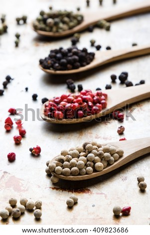 different color peppercorn seeds on wooden spoons on steel plate