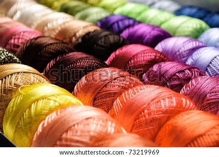 Different color threads on rows in the store - stock photo