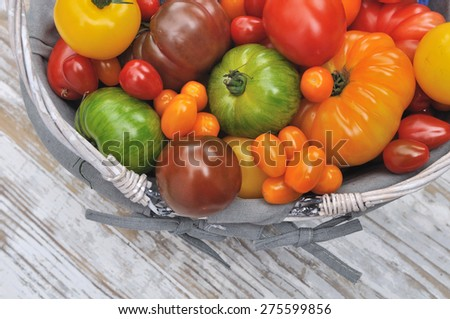 different color varieties of tomatoes in basket on white background wood - stock photo