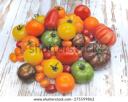 different color varieties of tomatoes on a wooden white table
