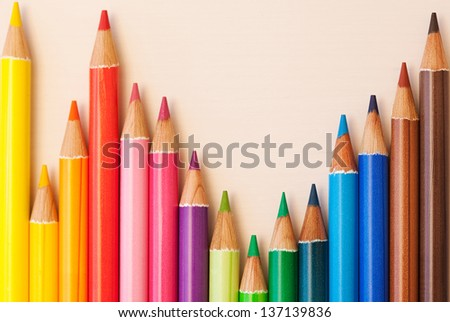 Different colored drawing pencils creating a statistics bars graph on a white writing desk, over head view. - stock photo