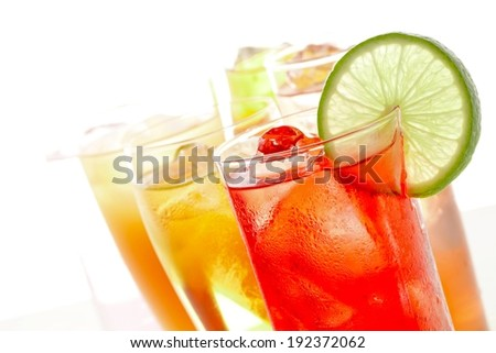 Different colored liquids in several glasses and one garnished with a lime. - stock photo