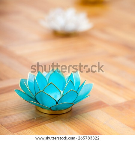 Different colored lotus candles on wooden floor - stock photo