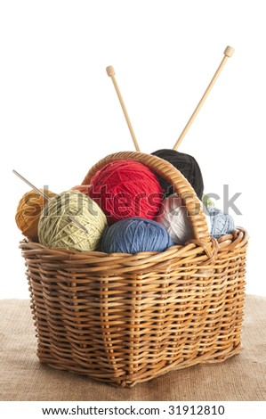 Different colored yarn in basket with knitting needle and crochet hook - stock photo