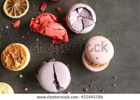Different colorful macaroons and dry orange slices on gray background - stock photo