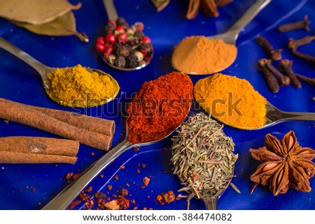 Different colorful spices in little spoons on dark blue background. Curry, turmeric, cinnamon sticks, bay leaves, sumac, cloves, peppercorn, paprika, rosemary, star anise. Top view. Closeup - stock photo