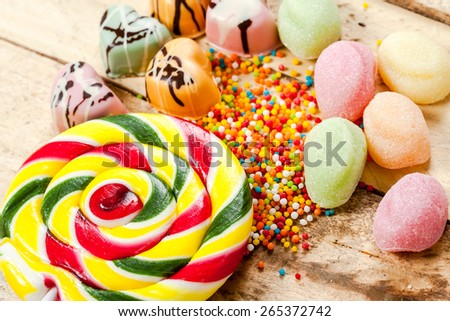 Different colorful sweets and lollipops on the wooden table.