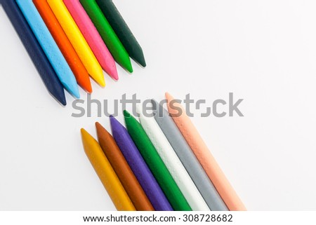 Different colors of crayons arranged in pattern on white background - stock photo