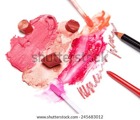Different colors of smeared and sliced lipstick, lip gloss with brushes, lip liner on white textured surface - stock photo