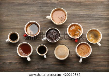 Different cups of coffee on wooden table, top view - stock photo
